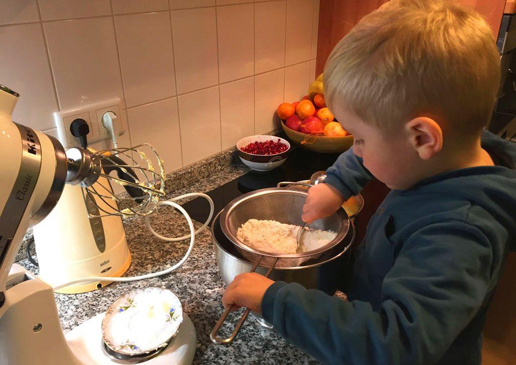 Der kleine Junge siebt das Mehl