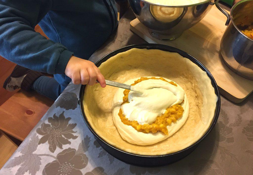 Kürbisfüllung und Käsecreme kommen nacheinander auf den Kuchenboden.