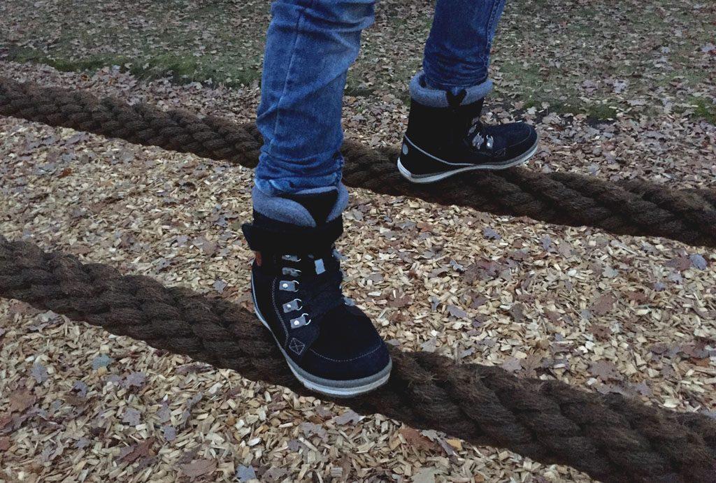 Der Junge klattert auf einem Klettergerüst. Die Stiefel werden in der Nahaufnahme gezeigt.