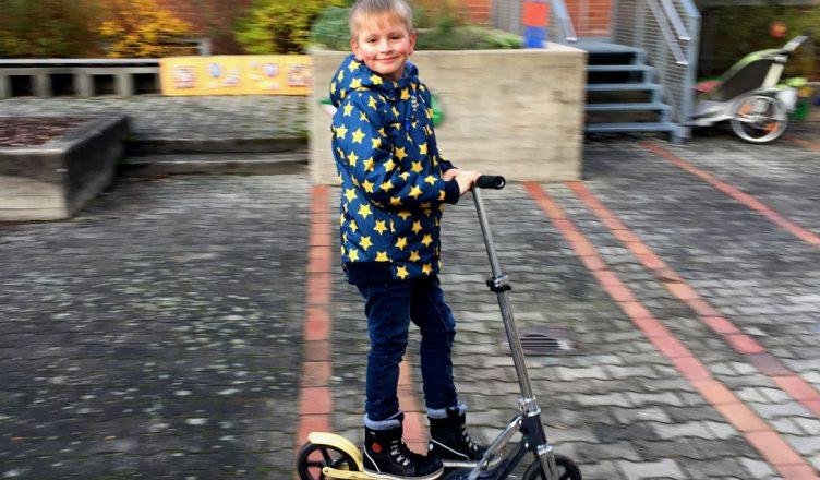 Der Junge fährt mit seinem Roller