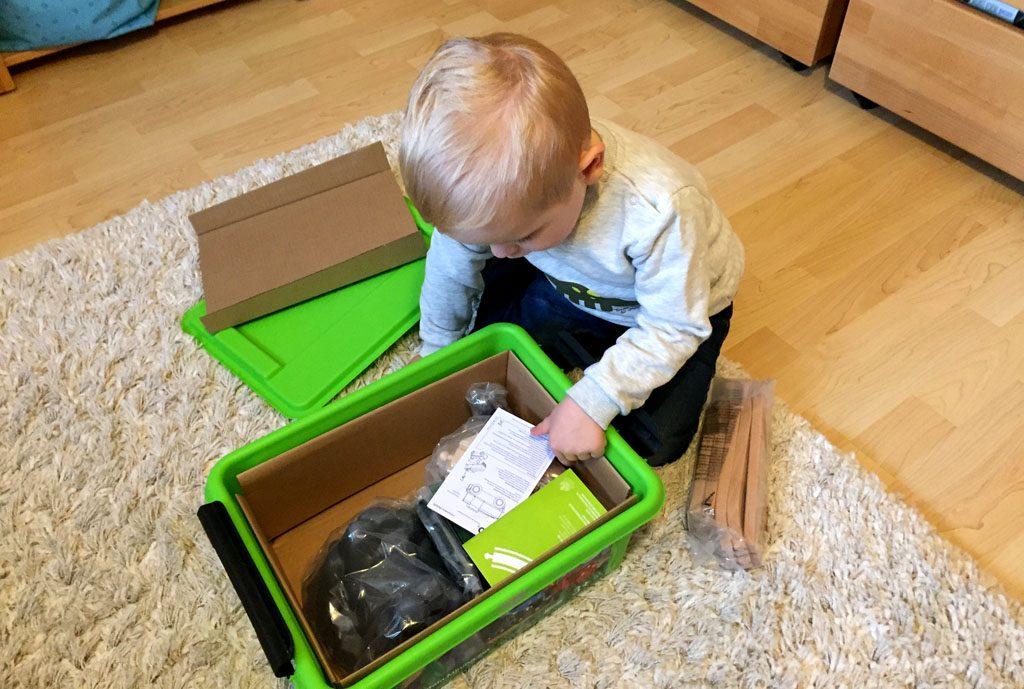 Der Junge betrachten den Inhalt der Aufbewahrungsbox.