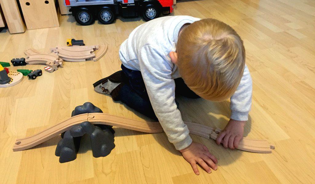 Der Junge baut die Eisenbahn zusammen.