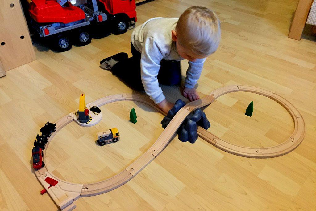 Der Junge spielt mit der Brio Eisenbahn.