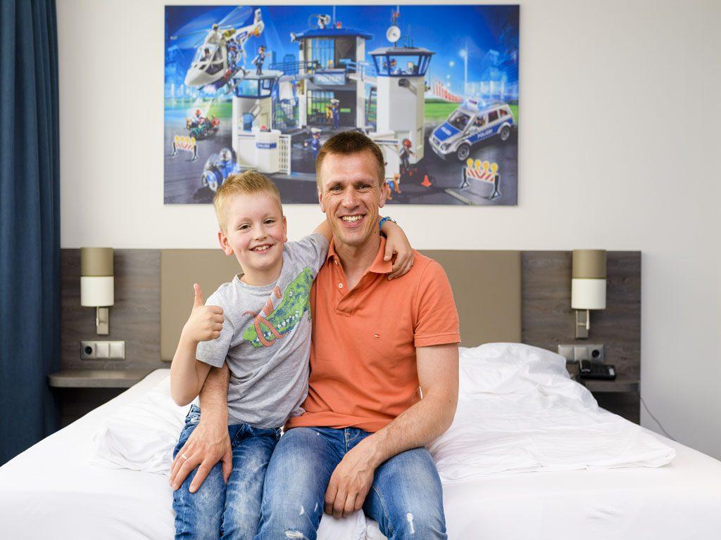 Papa und Sohn umarmen sich und sitzen dabei auf dem Bett