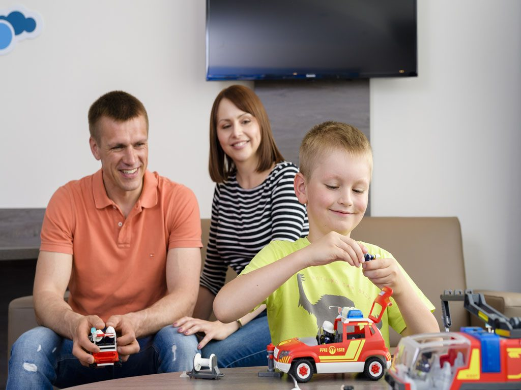 Der Junge spielt mit einem Feuerwehrauto, während die Eltern ihm dabei zuschauen