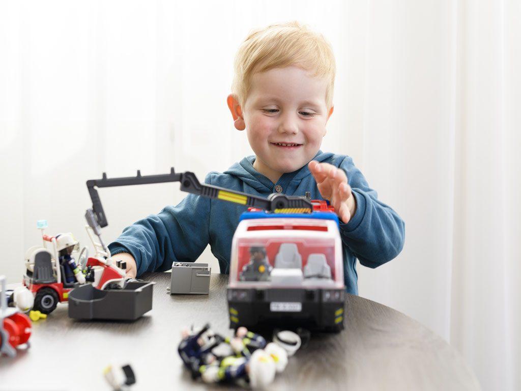 Der Junge spielt mit einem Feuerwehrauto
