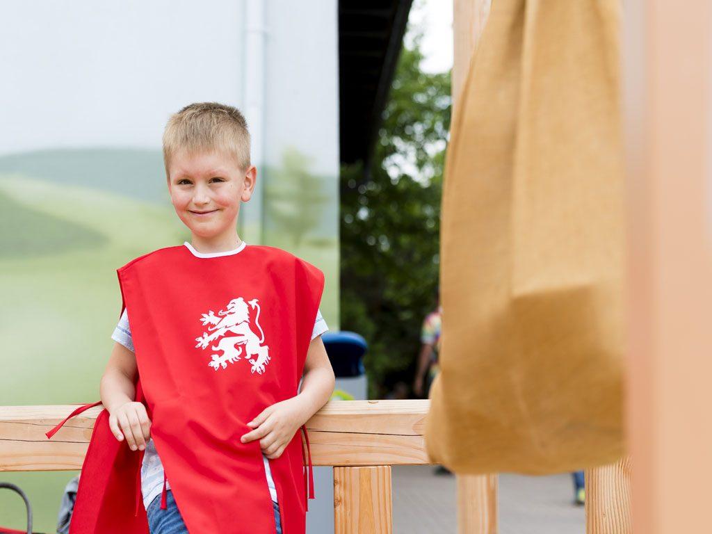 Ein lächelnder Junge, verkleidet als Ritter
