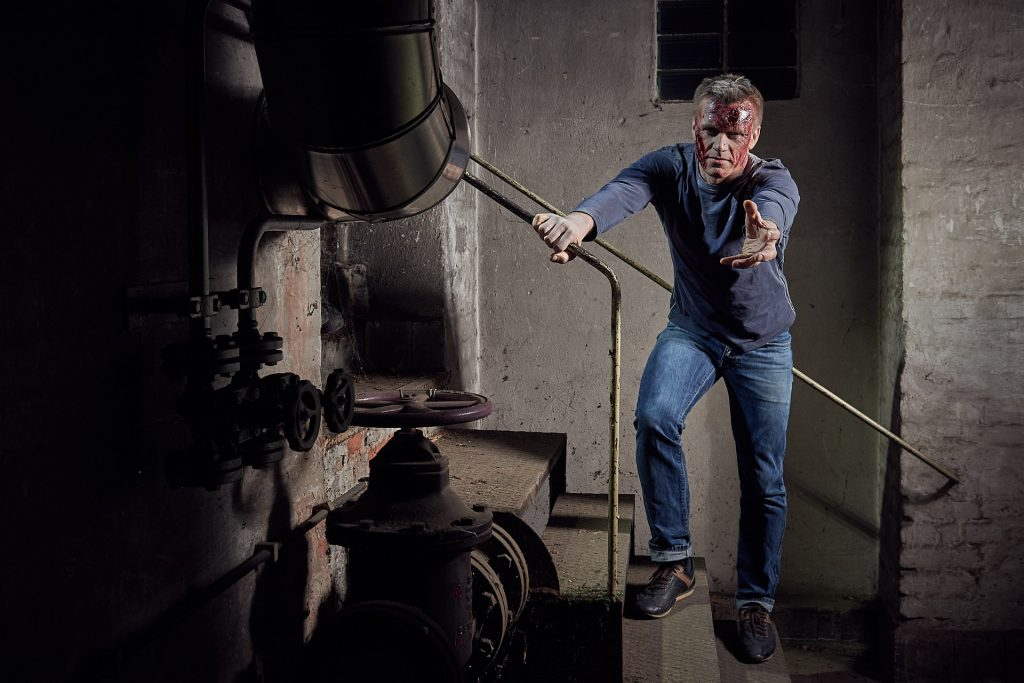 Ein männlicher Zombie steht auf der Treppe.