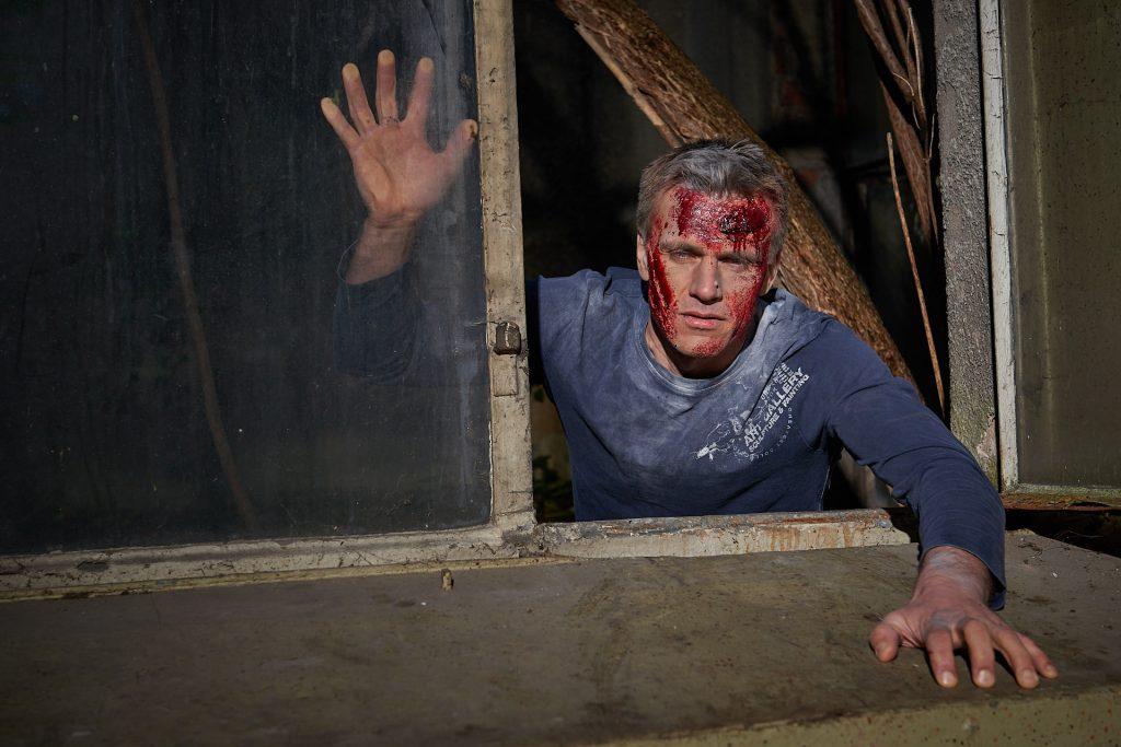 der männliche Zombie versucht durch ein Fenster in einen Raum zu gelangen.