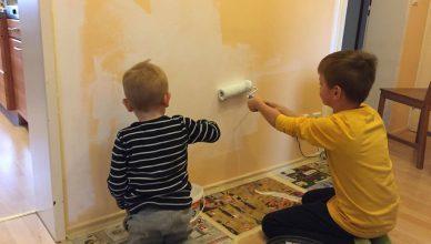 Die Jungs streichen eine Wand.