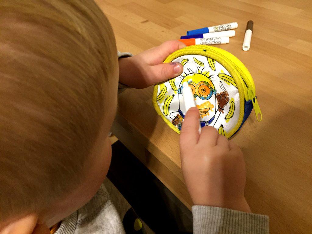 Der Junge bemalt den Minion mit gelbem Stift