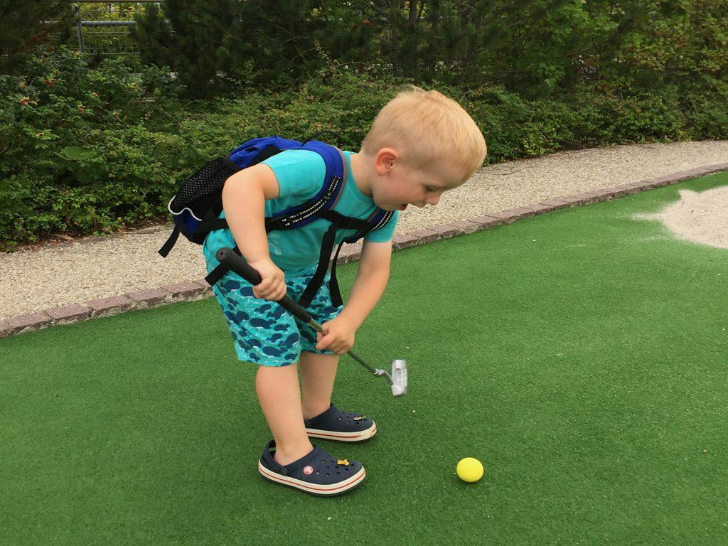 Der Junge spielt Minigolf