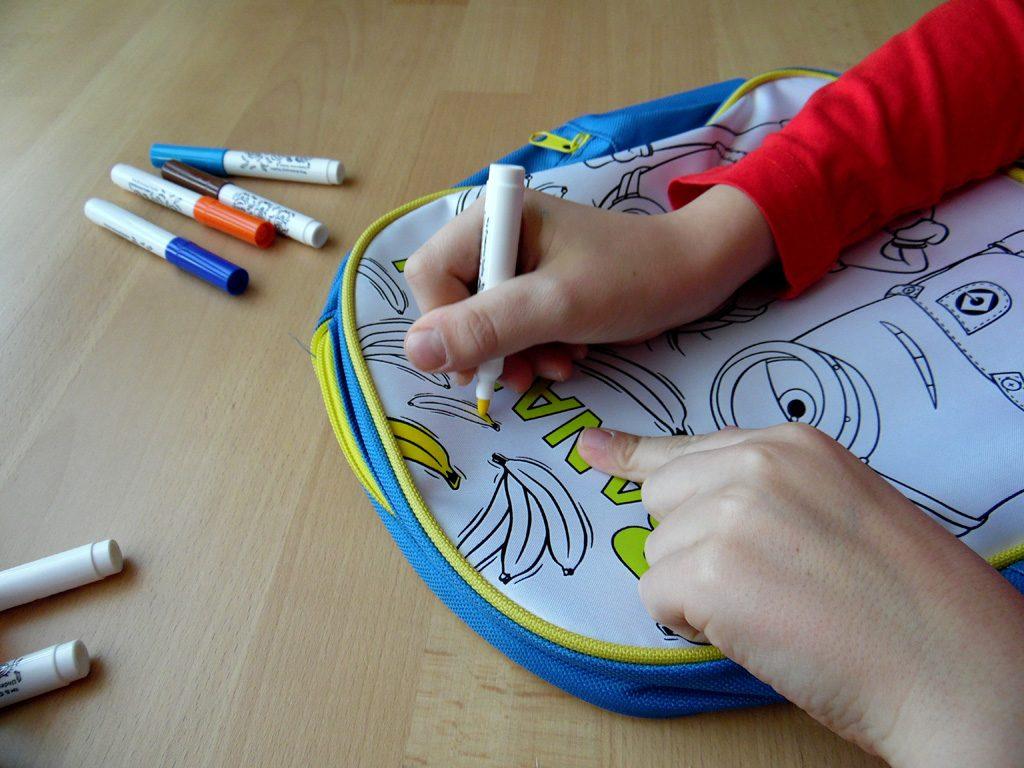 Der Junge malt die Banane auf dem Rucksack zum Bemalen aus