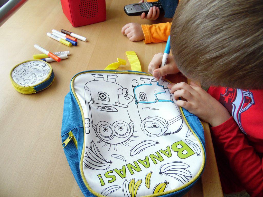 Der Junge malt die Hose von Minion auf dem Rucksack zum Bemalen aus