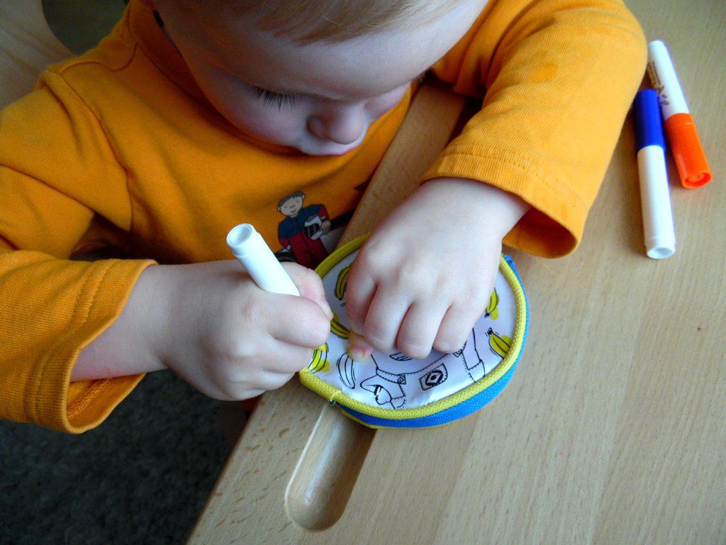 Der Junge malt die Banane auf dem Geldbeutel zum Bemalen aus
